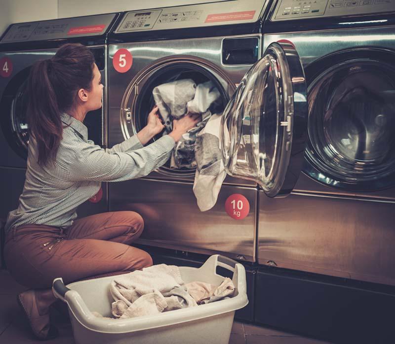ホテルのコインランドリーで洗濯する女性